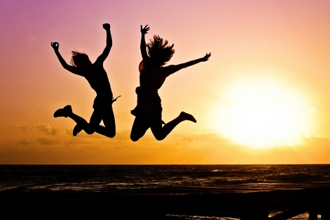 Two people jumping for joy at a beach during sunset